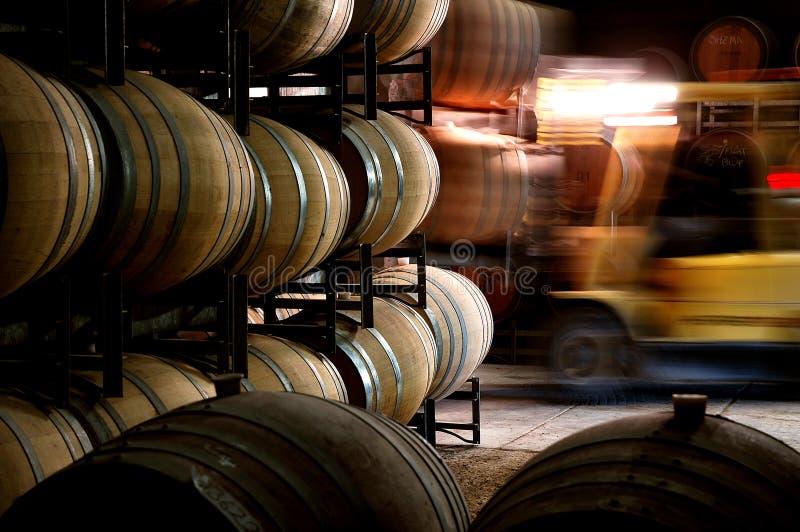 历史葡萄酒桶照片在有铲车的酿酒厂地窖里 库存照片