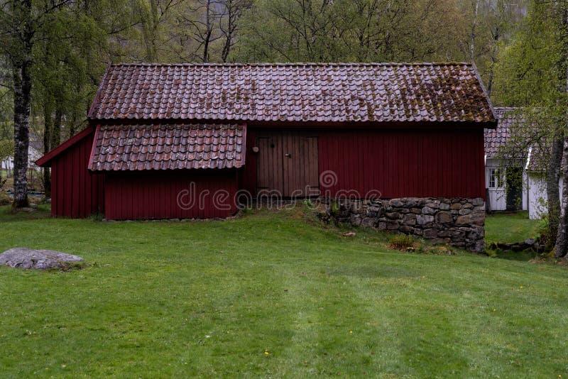 历史,传统红色谷仓在一个灰色春日 免版税库存照片