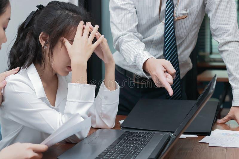 压下在办公室注重了年轻亚洲女商人覆盖物面孔遭受的手的上司 免版税库存照片