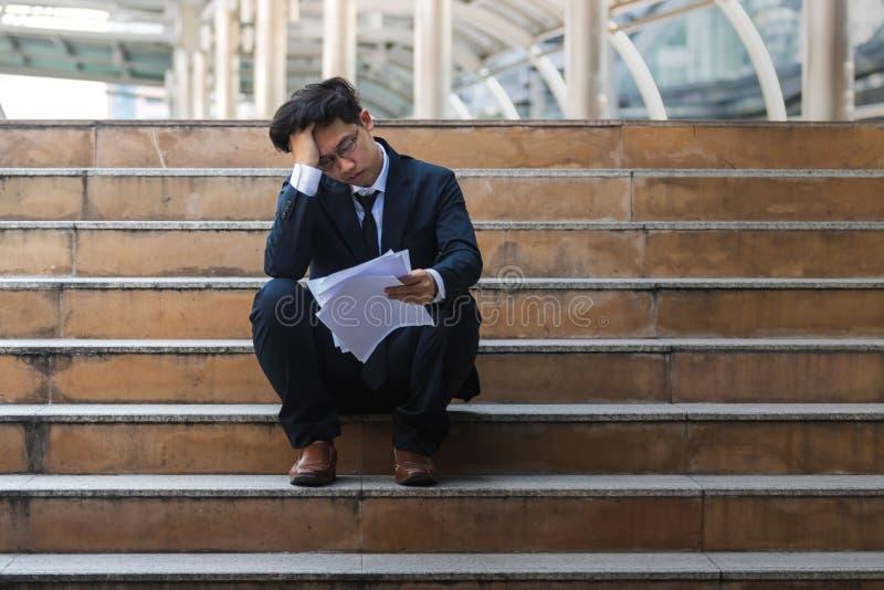 压下注重了衣服的年轻亚裔商人用在头的手坐台阶 失业和临时解雇概念 免版税库存图片