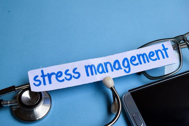 压力处理题字有听诊器、镜片和智能手机看法在蓝色背景 库存照片