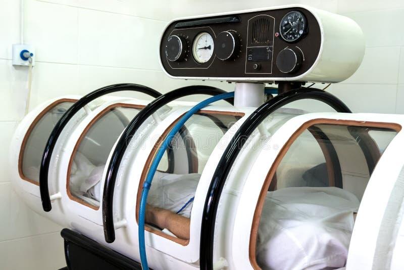 压力腔 人在一个白色压力室在 设备在医院或重病特护中心 库存图片