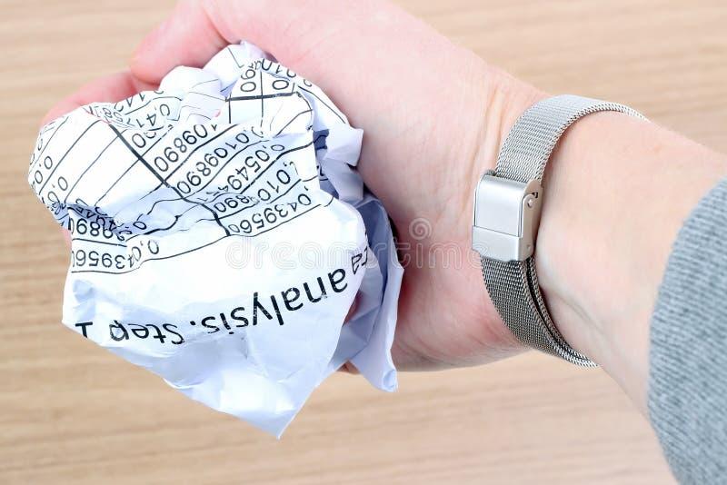 紧压在桌的女实业家一张被弄皱的纸 免版税库存图片