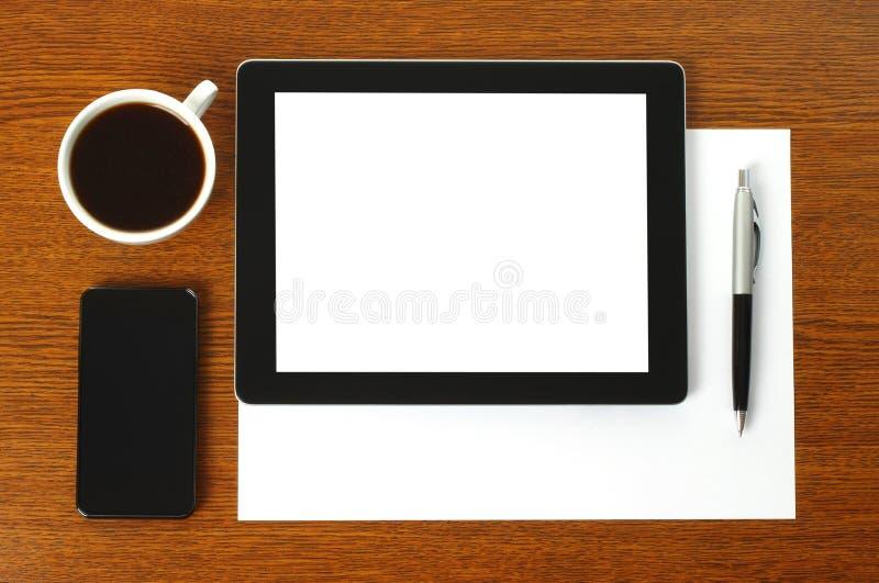 压片个人计算机、巧妙的电话、纸、笔和咖啡 免版税图库摄影