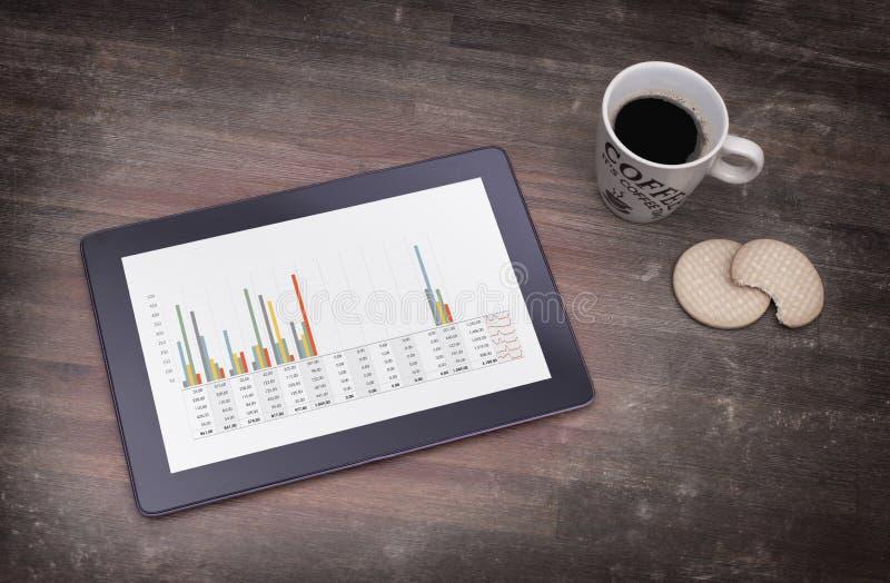 压片接触在木桌,图表上的计算机小配件 免版税库存照片