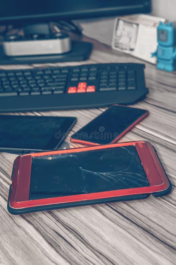 压片有残破的玻璃的计算机,说谎在有电话和其他小配件的桌面上 免版税库存照片