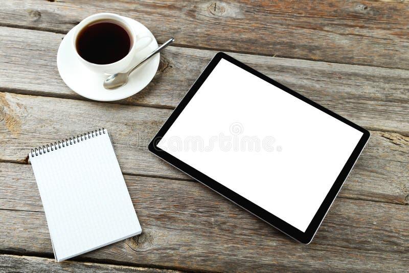 压片有笔记本和咖啡的计算机在灰色木b的 库存照片