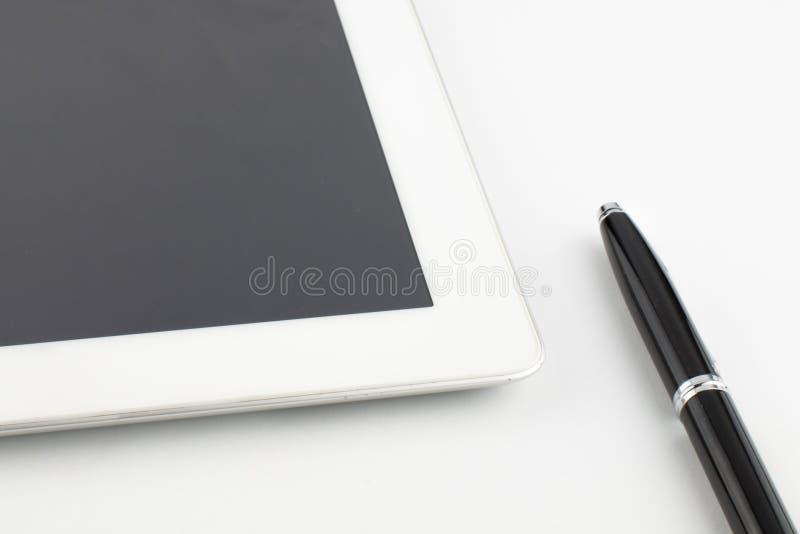 压片计算机和一支现代金属黑银笔在白色背景 库存图片
