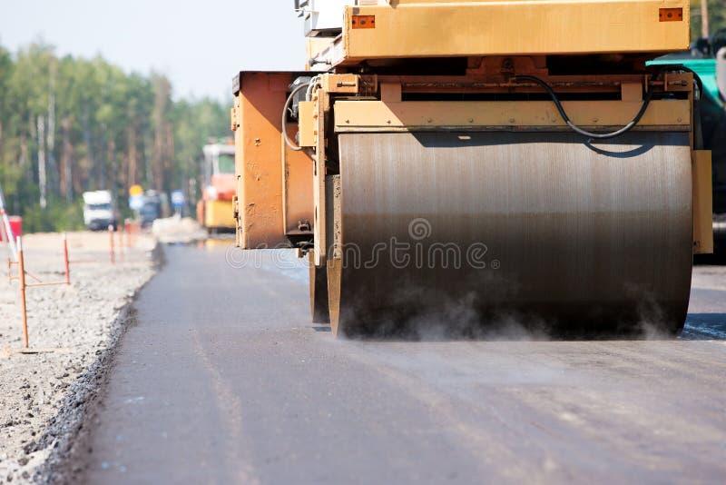压路机变紧密的沥青路面 库存照片