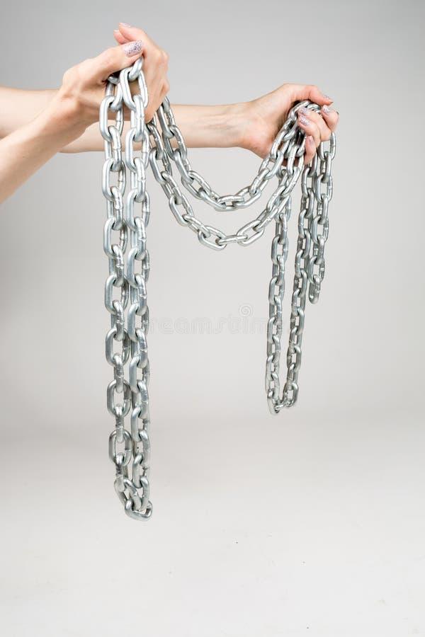 厚实的金属链子在被隔绝的白色背景的妇女的手上 免版税图库摄影