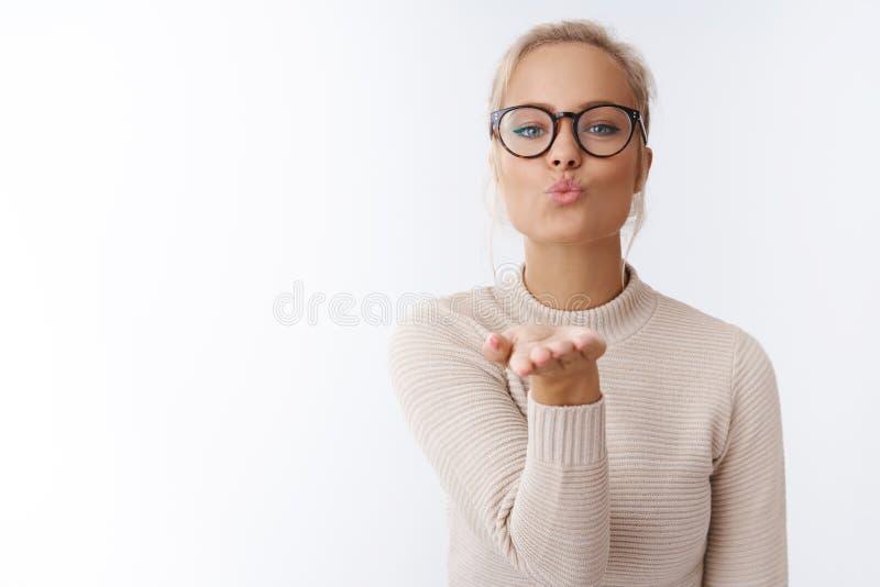 厚脸皮和逗人喜爱的有被梳的头发戴着眼镜毛线衣的魅力白肤金发的妇女室内射击提供手折叠嘴唇 免版税库存照片