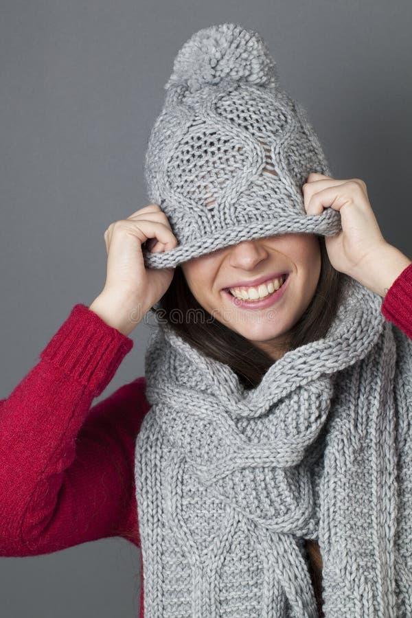 厚颜无耻的少年耍笑在掩藏在她的冬天帽子下 免版税图库摄影