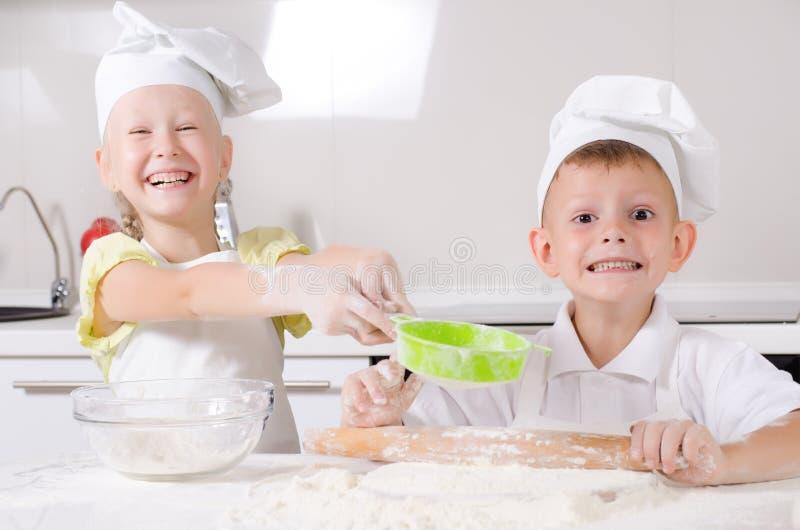 厚颜无耻的愉快的小男孩和女孩在厨房里 免版税库存照片