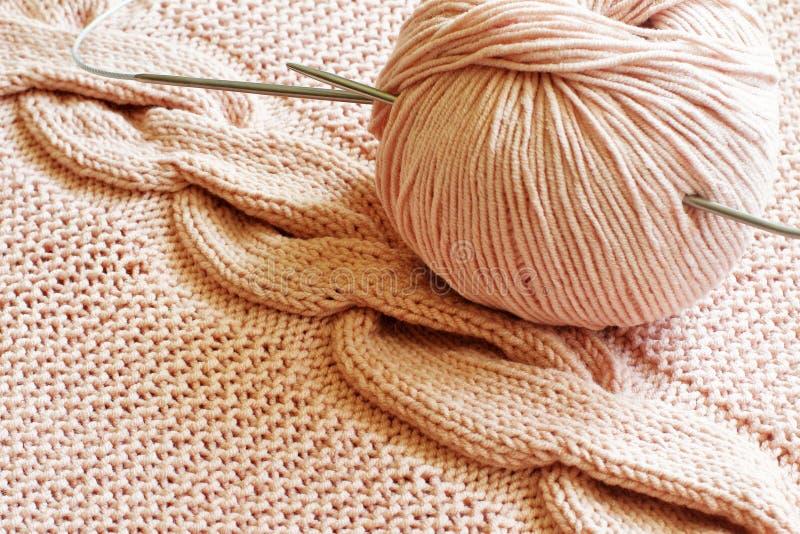 原始的手工编织的样式唾液的片段在桃红色棉纱品毛线后侧方和球的与钢编织针的 免版税库存图片