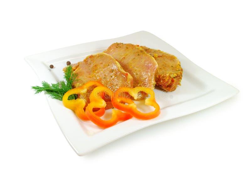 原始的肉 猪肉与sause的一片无骨的肉切片在盘被隔绝反对白色背景 库存图片