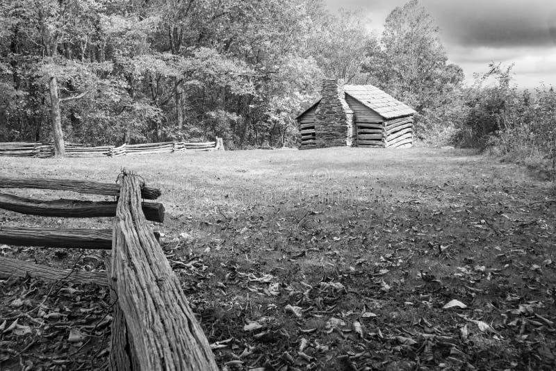 原木小屋和风雨如磐的云彩在蓝岭山行车通道 免版税库存照片