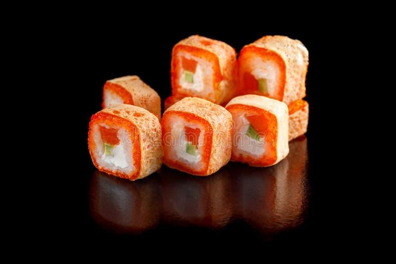 原物套寿司用飞鱼和费城乳酪鲕梨三文鱼鱼子酱在一个黑背景特写镜头 库存照片
