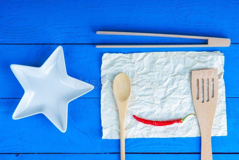 厨具和辣椒在纸片 免版税库存照片