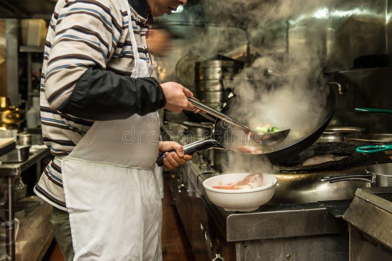 主厨在火炉的餐馆厨房里与平底锅 免版税图库摄影