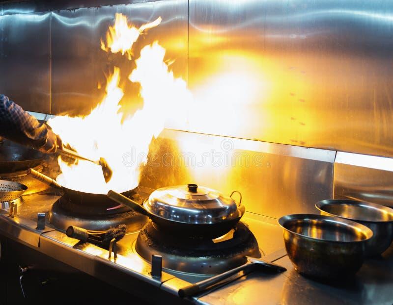 主厨在火炉的餐馆厨房里与平底锅 库存图片
