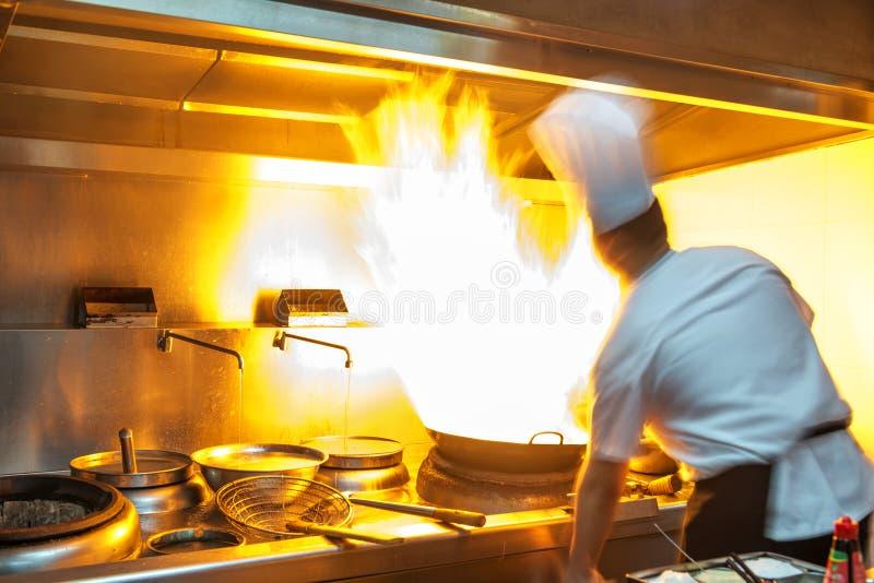 主厨在火炉的餐馆厨房里与平底锅 免版税库存照片