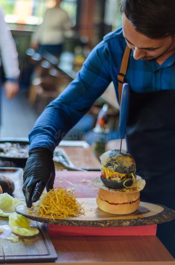 厨师他的汉堡为服务做准备 库存图片