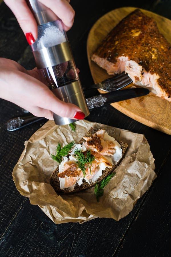 厨师以子弹密击与熏制鲑鱼内圆角的荷兰芹三明治在黑面包用软干酪 免版税库存照片