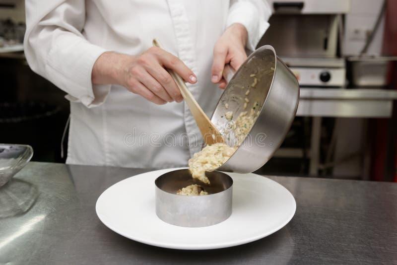 厨师供食意大利煨饭 免版税库存照片