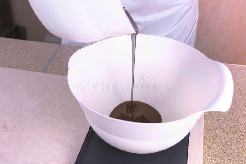 厨师倒在一个白色碗的液体黑暗的巧克力,站立在等级 关闭上色百合软的查阅水 免版税库存图片