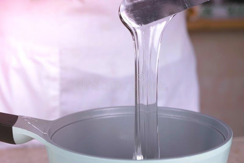厨师倾吐液体甘油入平底深锅重新加热 关闭上色百合软的查阅水 库存图片