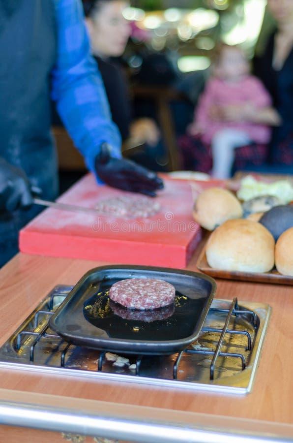 厨师准备在桌上的一个汉堡 库存图片