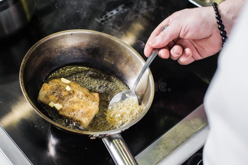 厨师准备大比目鱼在芹菜下在餐馆厨房里 免版税库存照片