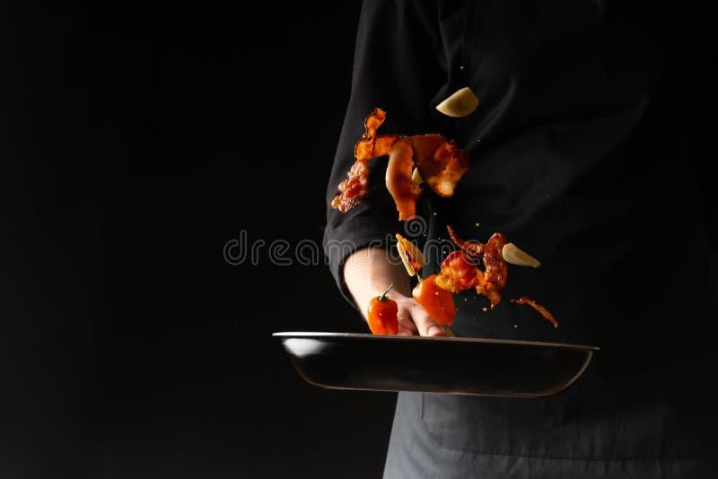 厨师准备烟肉切片用大蒜和辣子在平底锅,冻结在天空中,在黑背景,食谱书,菜单 库存图片