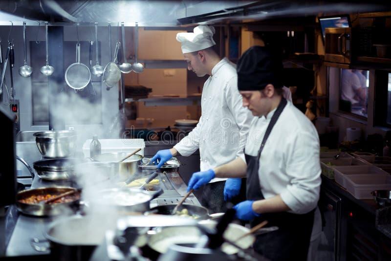 厨师准备食物的小组在餐馆的厨房里 免版税库存图片
