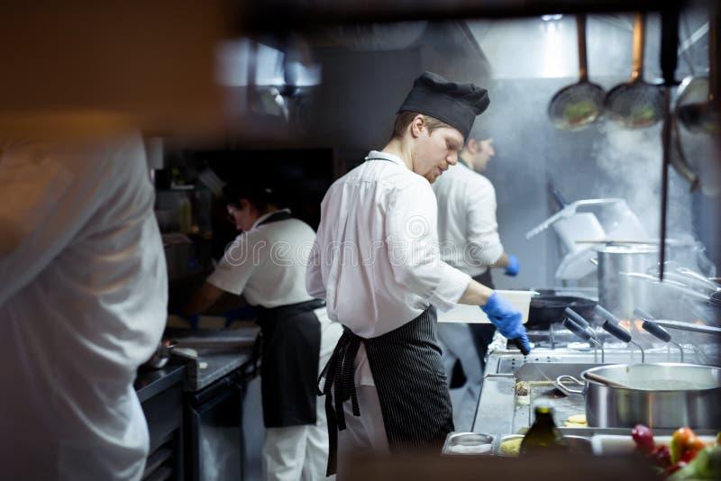 厨师准备食物的小组在餐馆的厨房里 图库摄影