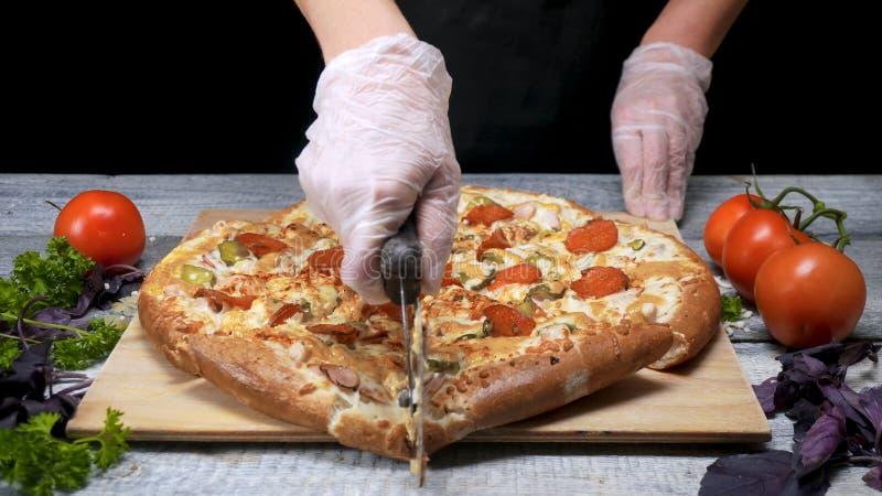 厨师切与路辗刀子的比萨 ?? 厨师手套裁减路辗刀子新近地烘烤了比萨 切可口比萨 库存照片