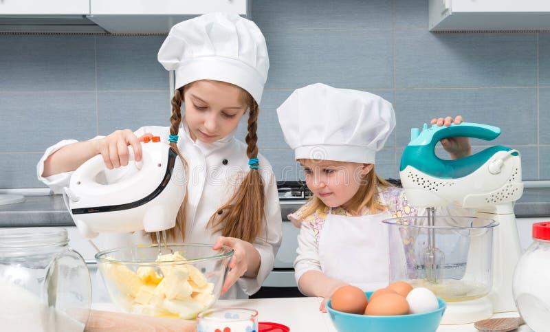 厨师制服的两个小女孩有在桌上的成份的 库存照片