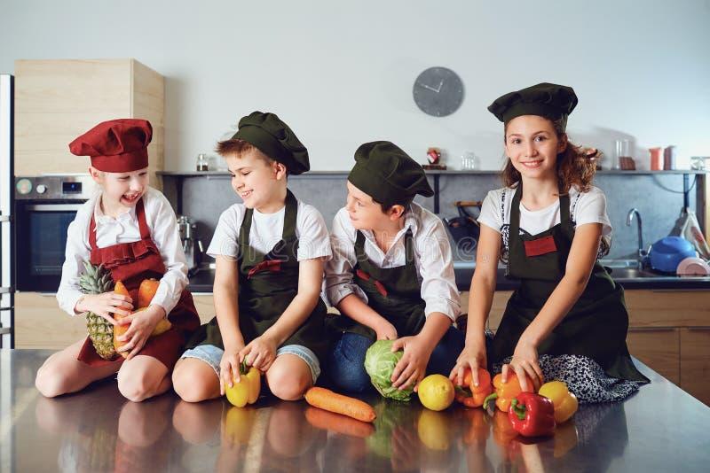 厨师制服的孩子在桌上的在t的菜 免版税库存照片