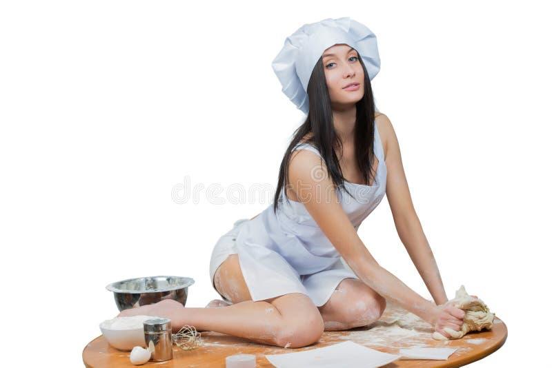 厨师制服的性感的妇女揉面团 库存照片