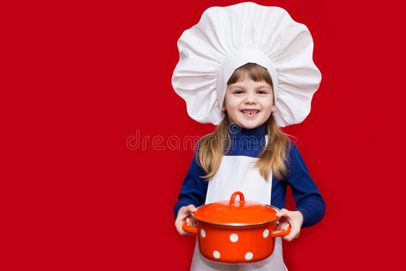 厨师制服的愉快的小女孩在红色拿着平底深锅被隔绝 孩子厨师 图库摄影