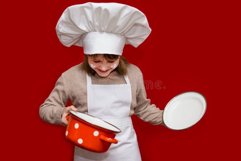 厨师制服的愉快的小女孩在红色拿着平底深锅被隔绝 孩子厨师 免版税库存图片