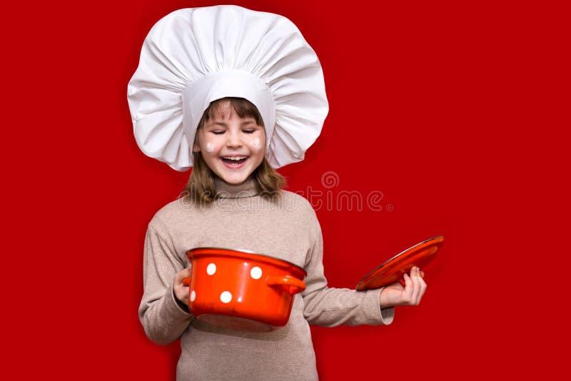 厨师制服的愉快的小女孩在红色拿着平底深锅被隔绝 孩子厨师 库存照片