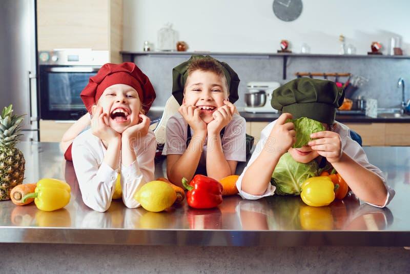厨师制服的滑稽的孩子在厨房里 免版税库存图片