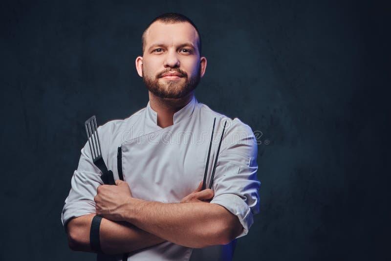 厨师厨师拿着在深灰背景的一把刀子 库存图片