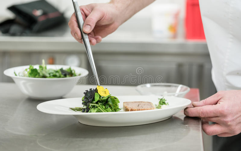 厨师厨师精整与夹子和flowe的沙拉和酥皮点心盘 免版税库存照片