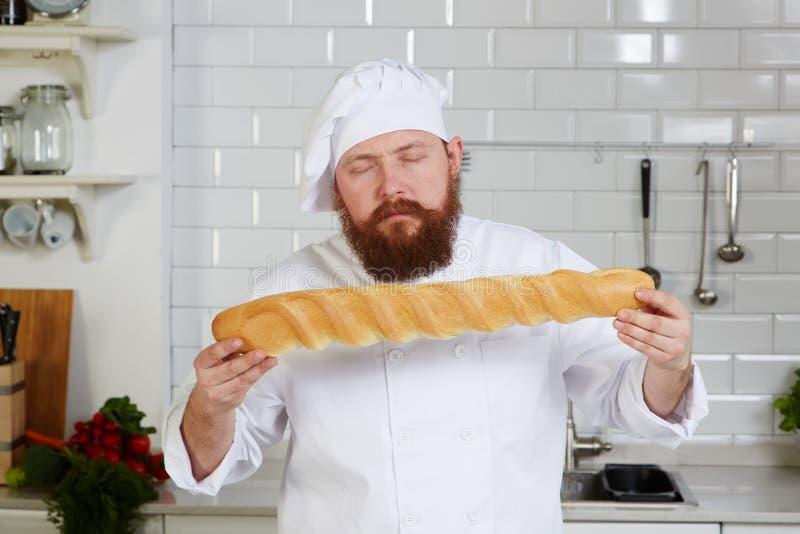 厨师厨师高级餐馆高兴地嗅新鲜面包的 免版税库存图片