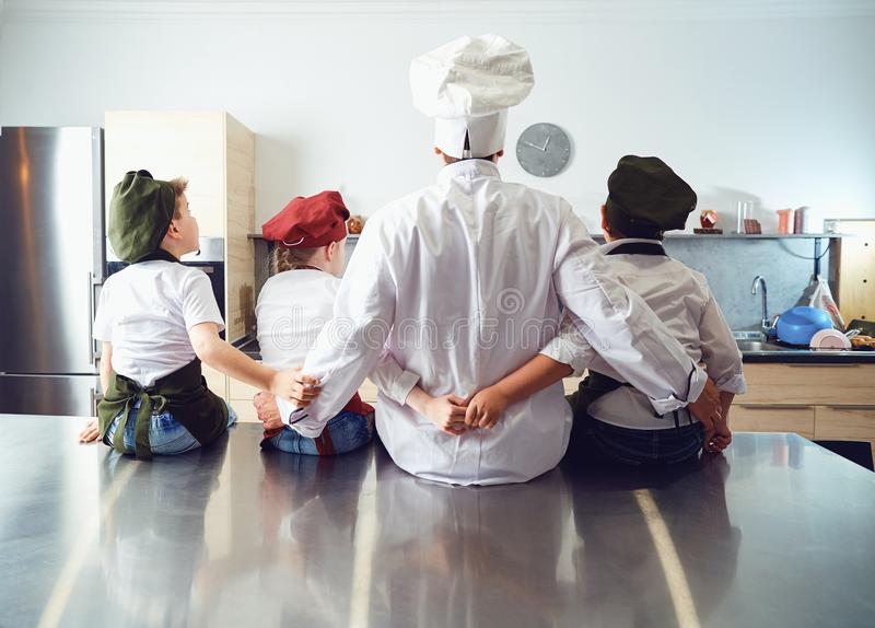 厨师和一个小组孩子在厨房里 图库摄影
