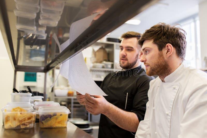 厨师和厨师有名单或票据的在厨房 库存照片