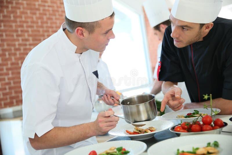 厨师和烹调学徒谈论 库存图片