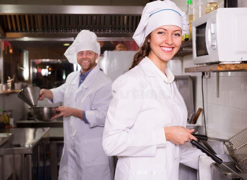 厨师和他的帮手小餐馆厨房的 库存照片